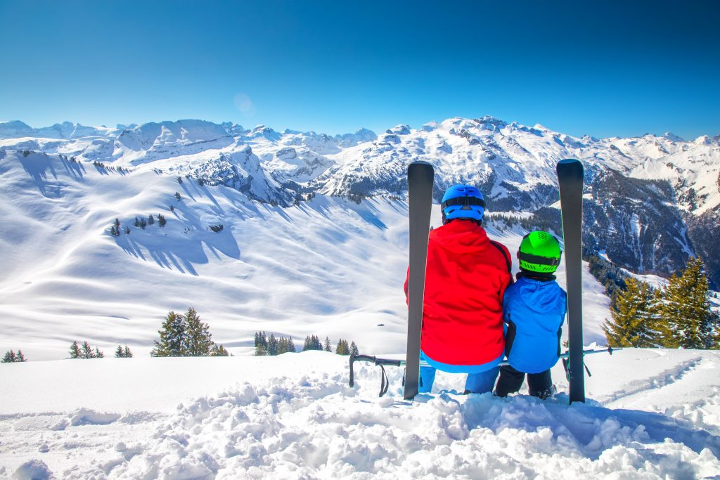 Father with his son skiing and enjoying the view of Swiss Alps, Hoch Ybrig, Switzerland, Europe.