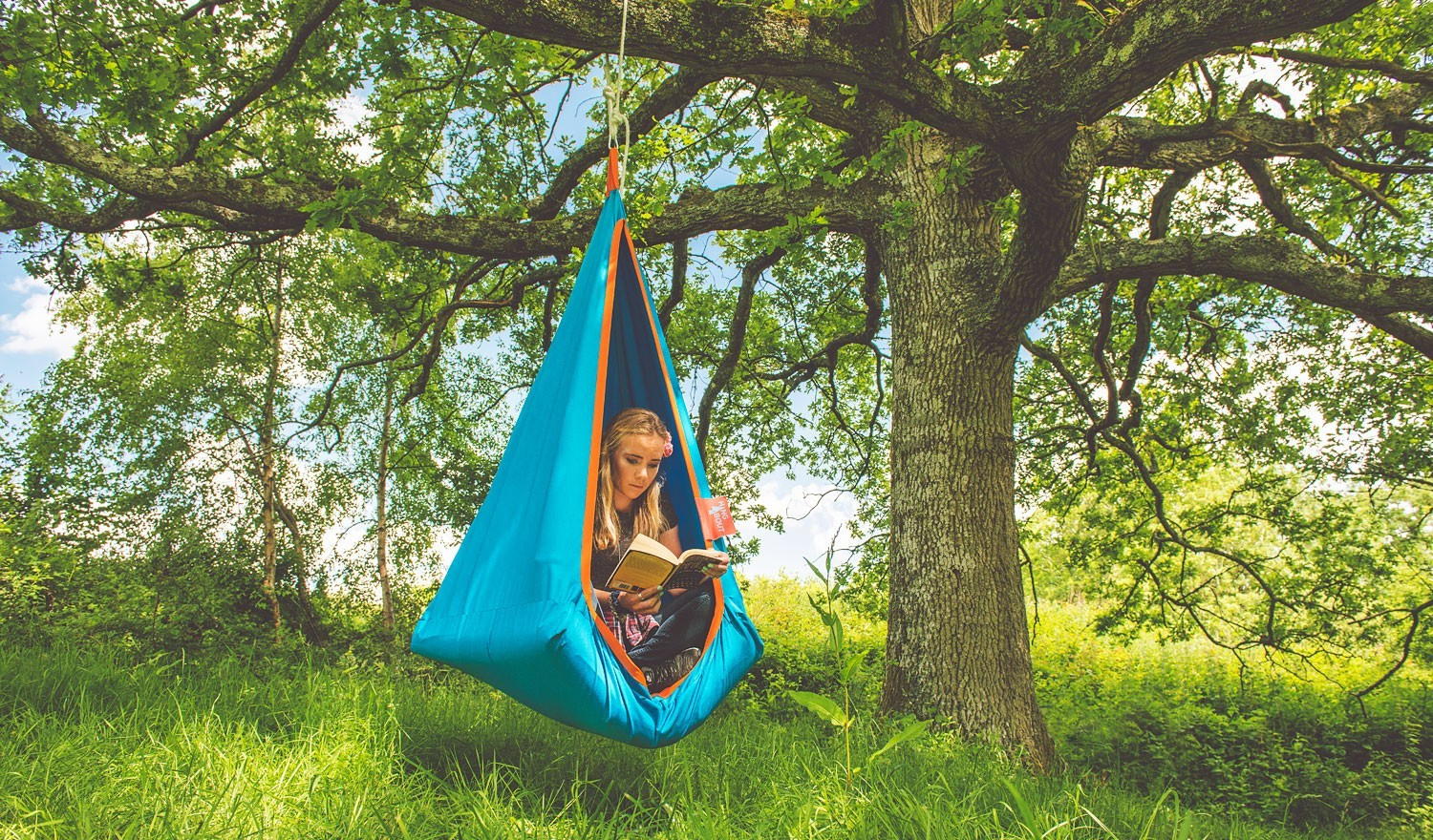 hang-about-blue-outdoor-hanging-chair-woman-reading-book_1-2